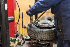Professional auto mechanic replacing tire on wheel in car repair service Stock Photos