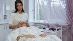 Beautiful cosmetologist giving a young woman facial massage at beauty spa Stock Footage
