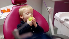 Cute little boy with green apple in the dental clinic. Stock Footage