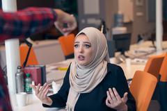 Worried arabic businesswoman wearing hijab receiving a notification Stock Photos