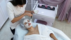 Beautiful woman getting facial mask at beauty salon Stock Footage
