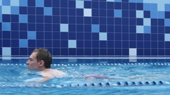 Fit swimmer doing the breaststroke in a swimming pool Stock Footage