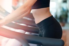 Woman with bottle of water exercising on treadmill in gym Stock Photos