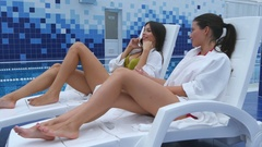 Happy brunette woman talking on the phone on deckchair with her smiling female Arkistovideo