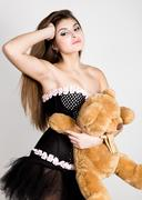 Sexy young woman in very little black dress holding a teddy bear Kuvituskuvat