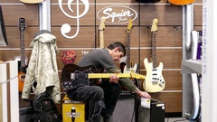 People playing guitar inside best buy store on boxing day sale Stock Footage