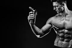 Muscular man with protein drink in shaker over dark background Stock Photos