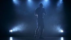 Coaching boxer male in a dark studio with rear lights Stock Footage
