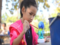 HD Close up shot asian little girl painting water color on doll Stock Footage