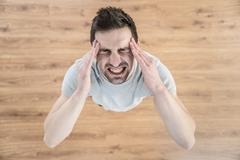 The man keep his head and scream from pain Stock Photos