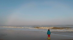 Boy on beach looking at white rainbow - Fog bow -  over misty sea in Norfolk Stock Footage