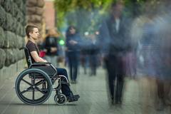 The invalid man sit in the wheel chair in the crowd stream at sidewalk Stock Photos