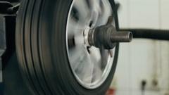 Tire service. Mechanic balancing a car wheel on automated machine. Stock Footage