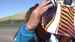 A teenage girl motocross rider putting on helmet as she prepares to ride motocro Stock Footage
