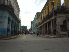 Old colonial dilapidated buildings with columns near the road in Havana Stock Footage