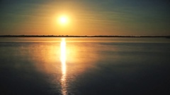 Time lapse of sun rising over water at dawn with morning mist Stock Footage