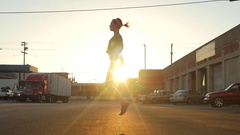 Silhouette of a young woman jump roping in the streets of an urban environment, Stock Footage