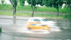 Many cars driving on road flooded with water during rain Stock Footage