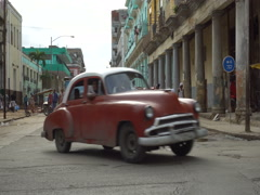 Movement of red retro car near colonial building with columns in Havana Stock Footage