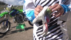 A teenage girl motocross rider putting on gloves as she prepares to ride motocro Stock Footage
