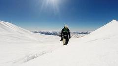 Freeride snowboarder climbing mountain on sunny winter day Stock Footage
