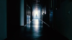 Scientist in protective suit going through dark corridor Stock Footage