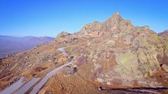 Mountain rocky summit aerial low grass autumn skyline peak sunny day blue sky Stock Footage