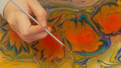 Child hand is painting on water with idle. Ebru Painting. Stock Footage