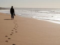 Silhouette of a woman walking alone at the beach feeling lonely Stock Photos