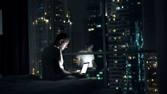 Young man browsing web on laptop sitting on bed at home at night Stock Footage