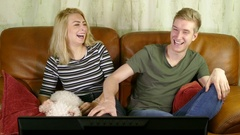 Young couple watching TV and laughing. Stock Footage