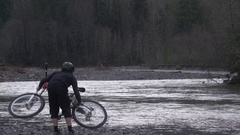 A young man mountain biker holding bike over his head. Stock Footage