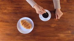 Woman drinking black coffee with croissant on breakfast Stock Footage