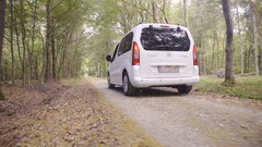 White minivan car driving inside the forest on gravel pathway 4K Stock Footage