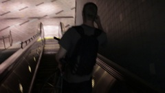 A young man taking an escalator down to the metro station while holding his bike Stock Footage