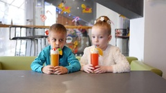 Milkshake cocktail - children in cafe, cute little girl and boy drink from straw Stock Footage