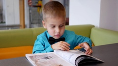 Cute little boy leafing a paper magazin sitting at cafe table Stock Footage