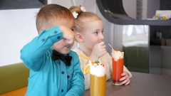Milkshake cocktail - children in cafe cute little girl and boy eat cream topping Stock Footage
