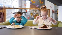 Cute kids in cafe, boy and girl funny eating sweet pieces of cake with forks Stock Footage