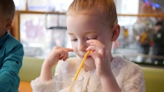 Milkshake cocktail - children in cafe, cute little girl lick cream from straw  Stock Footage