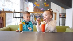 Milkshake cocktail - children in cafe cute little girl and boy funny drink straw Stock Footage