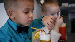 Cute little boy and girl in cafe with milkshake cocktail eat a cream topping Stock Footage