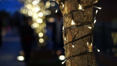 Beautiful holiday illumination tree trunk decorated with Christmas light Stock Footage
