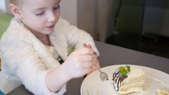Cute kid girl in cafe eat a piece of cake with a fork Stock Footage
