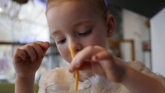 Cute little girl in cafe with milkshake cocktail lick a cream foam from straw Stock Footage