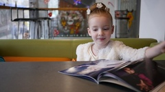 Cute little kid girl leafing a paper magazin sitting at cafe table slow motion Stock Footage