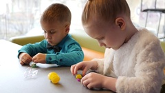 Cute kids in cafe, children sit at table and play the kinder surprise toys Stock Footage