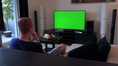 A man watches a TV with a green screen in a cozy living room, eventually looks Stock Footage