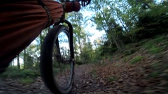 POV from bike pedal of man mountain biking through a European forest in the moun Stock Footage