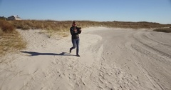 Wide tracking shot of lady using a tablet walking on the beach Stock Footage